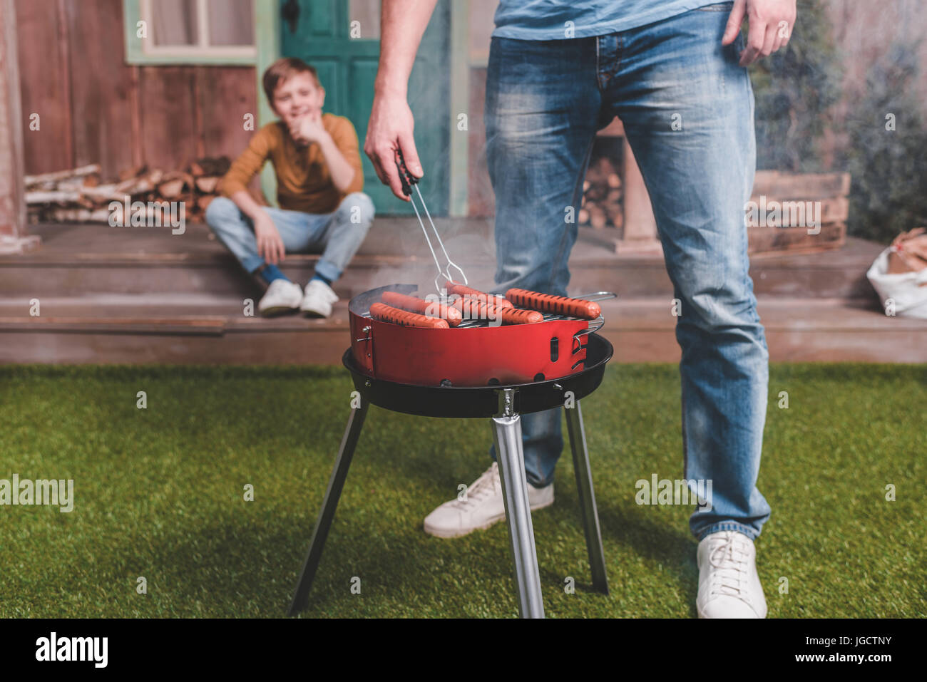 partial view of father cooking hot dog sausages with son behind - Stock Image
