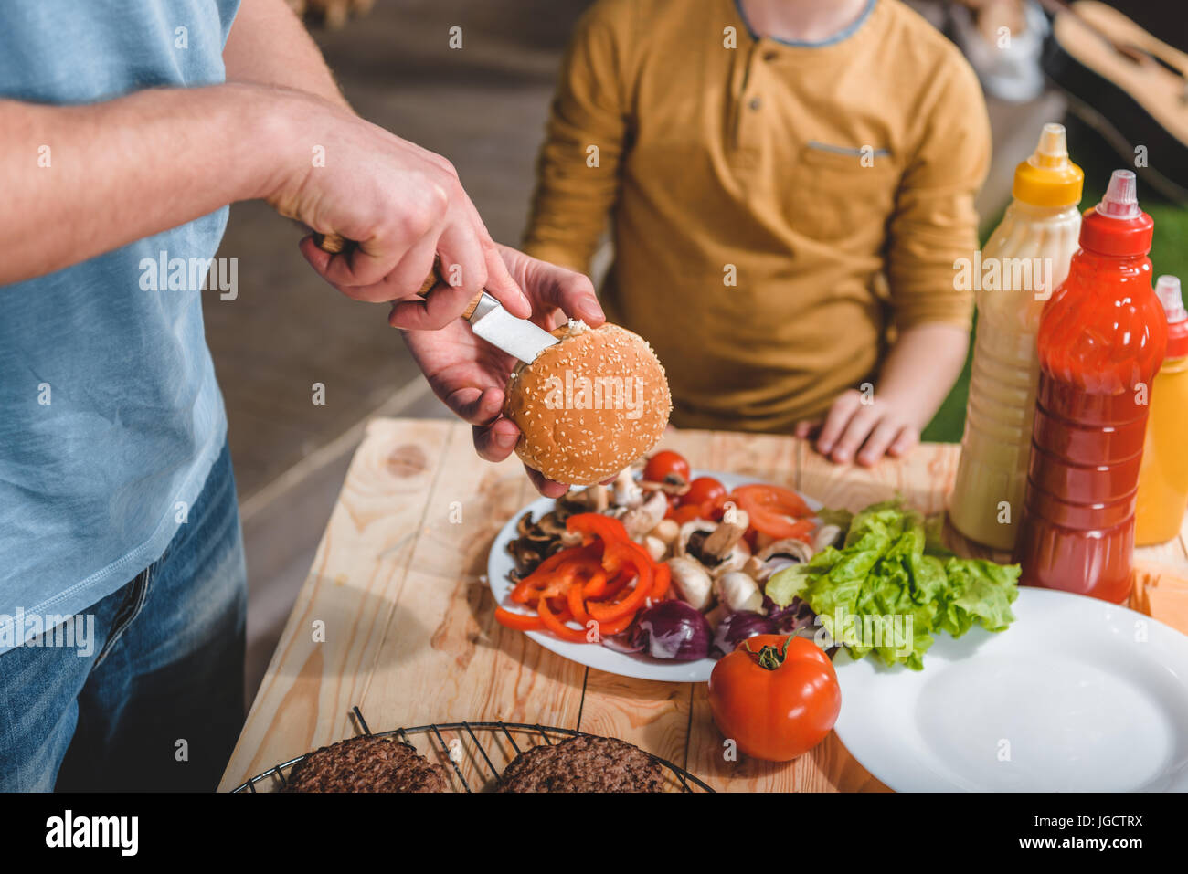 partial view of dad and son cooking meat burgers together - Stock Image