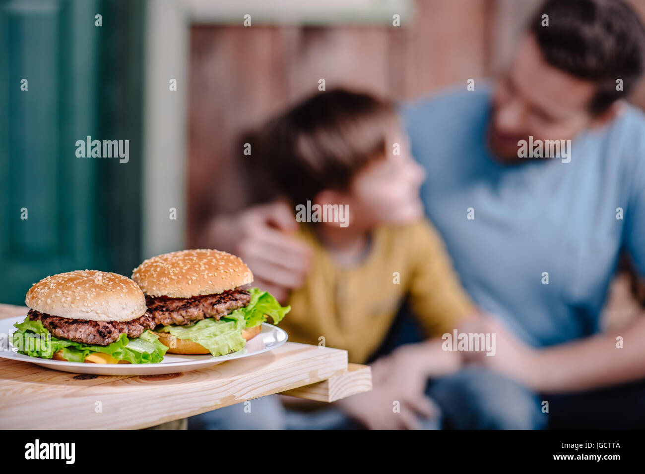 close up view of homemade burgers on plate with family behind - Stock Image