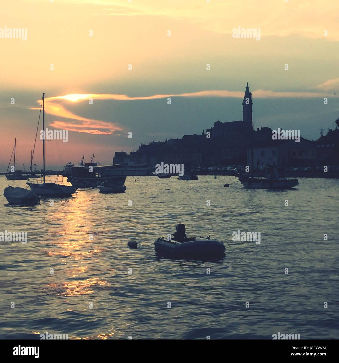 view of the sea and sunset behind the old town of Rovinj in Croatia - Stock Image