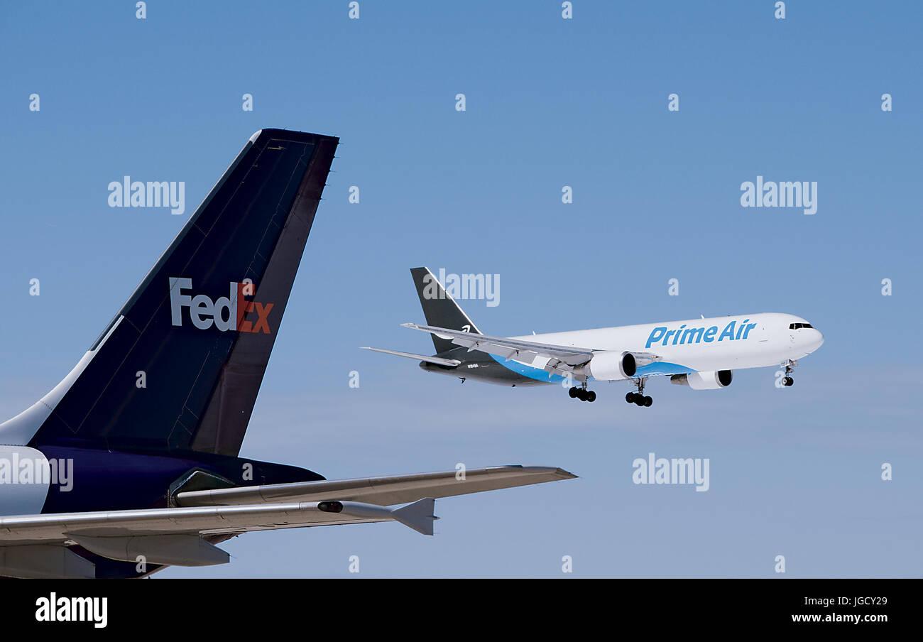 Amazon Prime Air Cargo Jet Landing Past FedEx Airplane Tail at Allentown, Pennsylvania - Stock Image