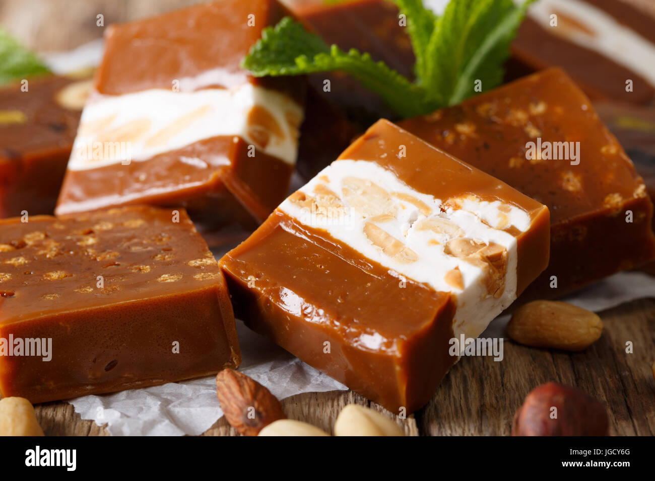 Candy toffee with almonds, decorated with fresh crumpled macro on parchment on the table. Horizontal - Stock Image