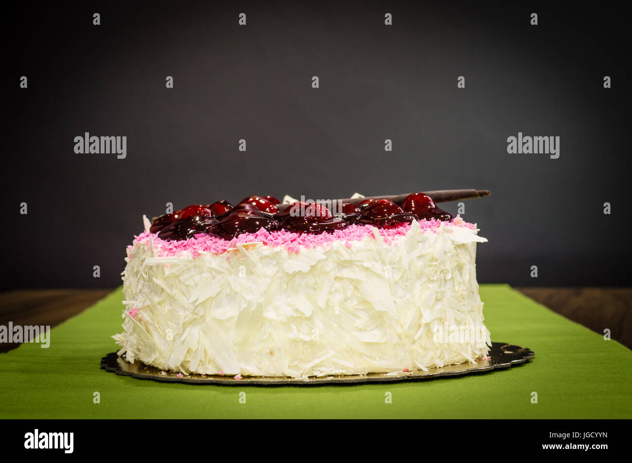 Delicious creamy whole white chocolate cake with cherries on top on a dark background Stock Photo