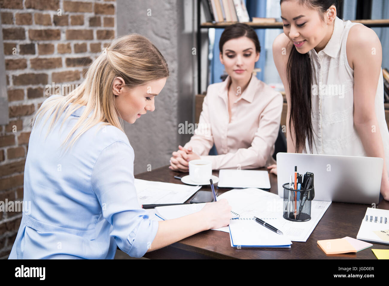 multicultural businesswomen discussing project and writing something in notepad at workspace - Stock Image