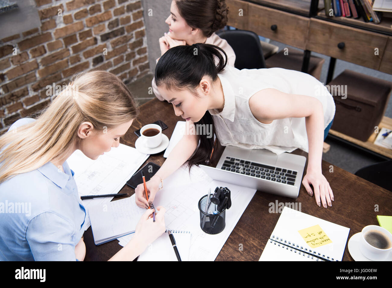 multicultural businesswomen discussing project and writing something in notepad together at workspace - Stock Image