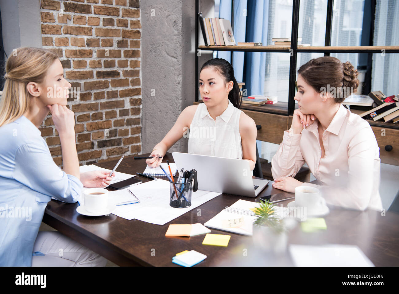 pensive multicultural businesswomen discussing business project at workplace with laptop - Stock Image