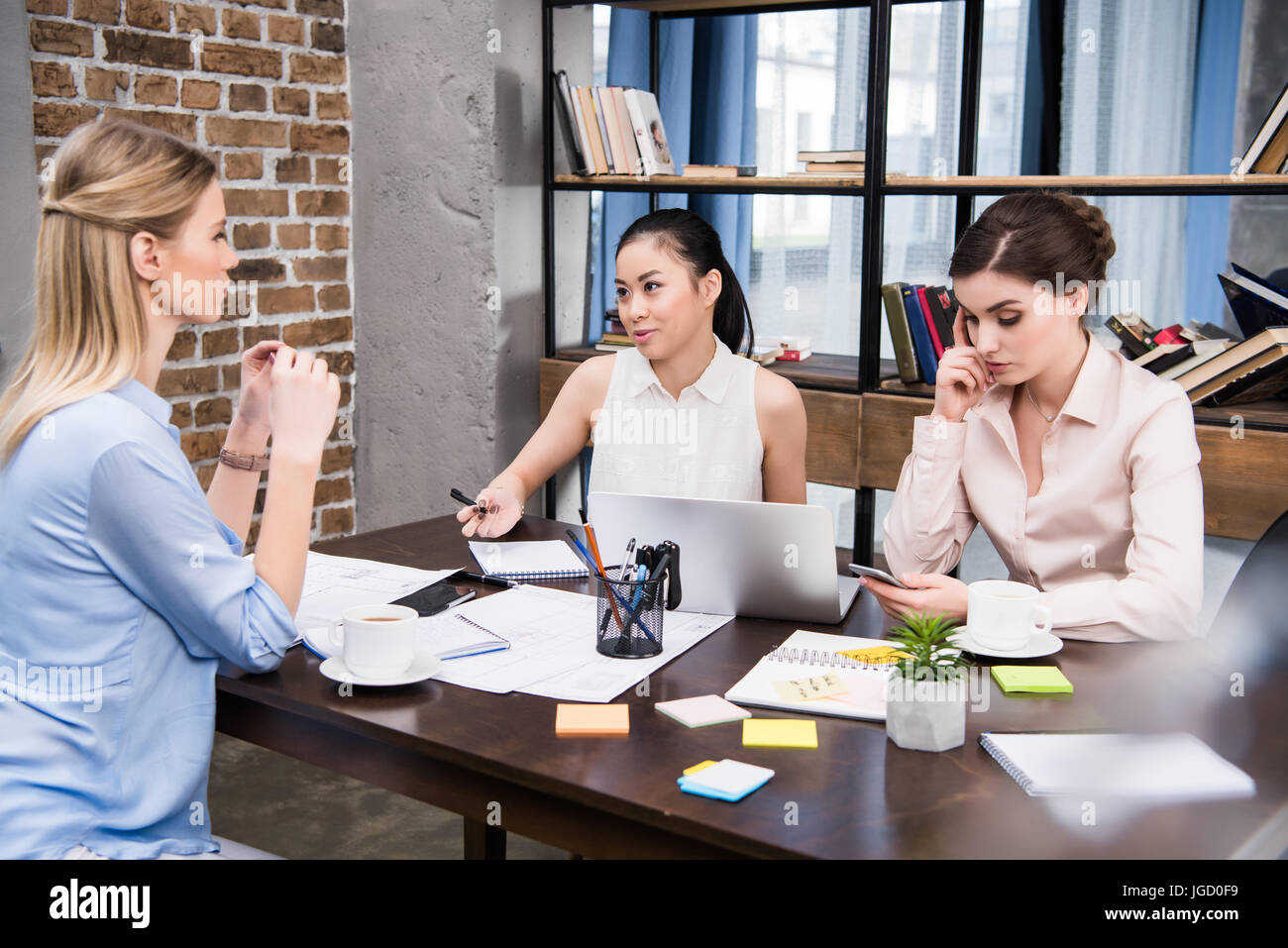 three multicultural businesswomen working and discussing project at workplace in modern office - Stock Image