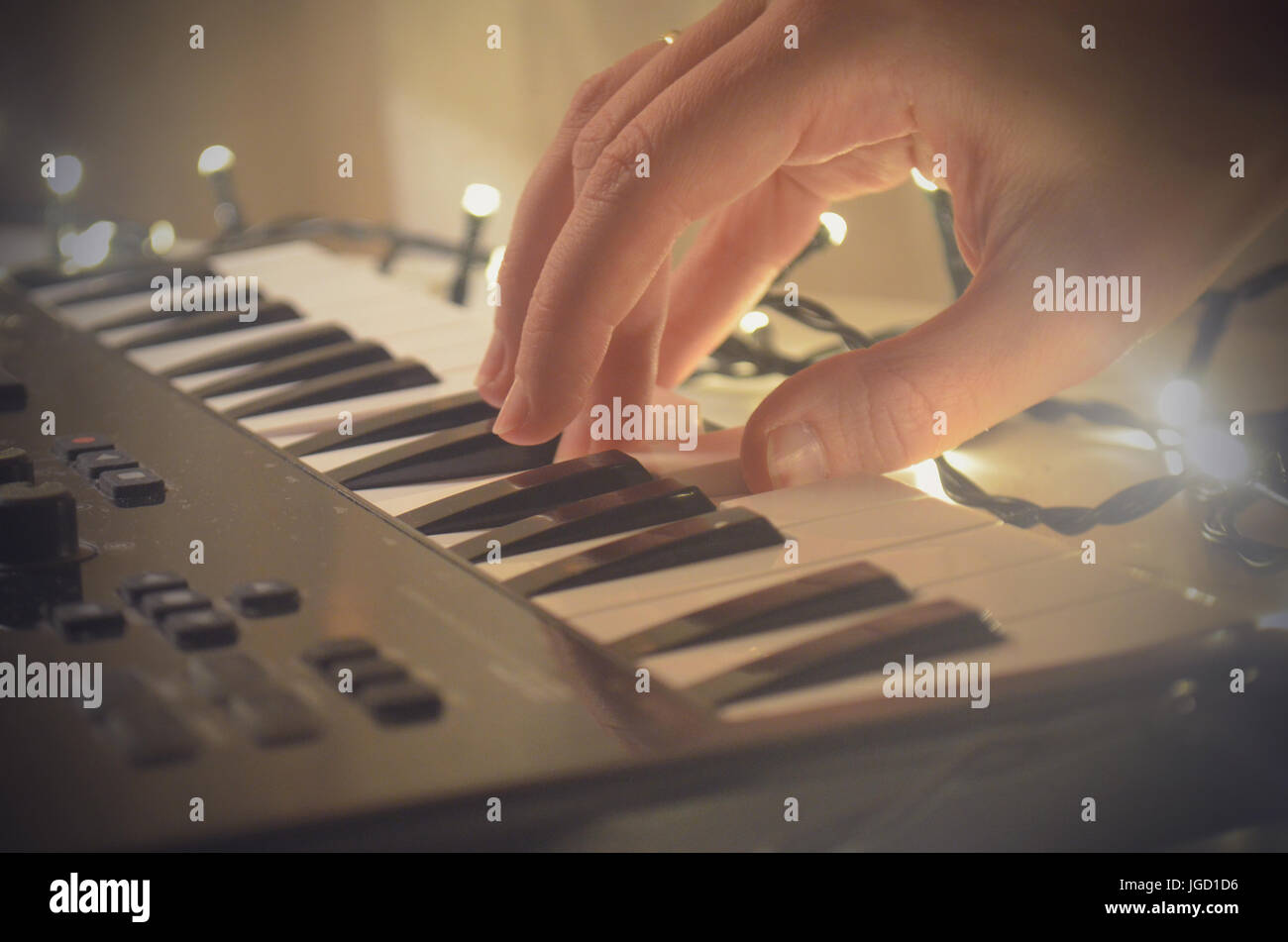 Woman hand playing Piano or electone midi keyboard, electronic musical synthesizer white and black key. - Stock Image