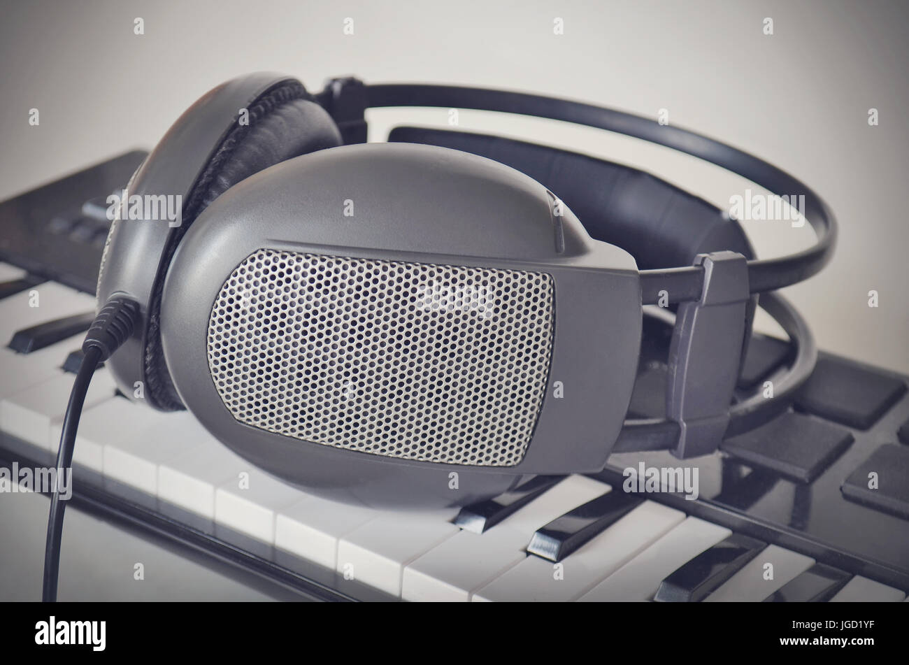 Headphones on electone midi keyboard. Close up. instagram filter style. - Stock Image
