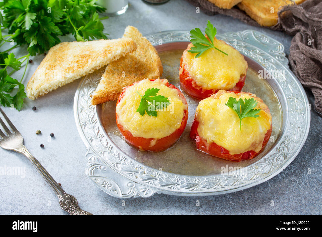 Stuffed tomatoes. Tomatoes baked with cheese and chicken, served with croutons of white bread. - Stock Image