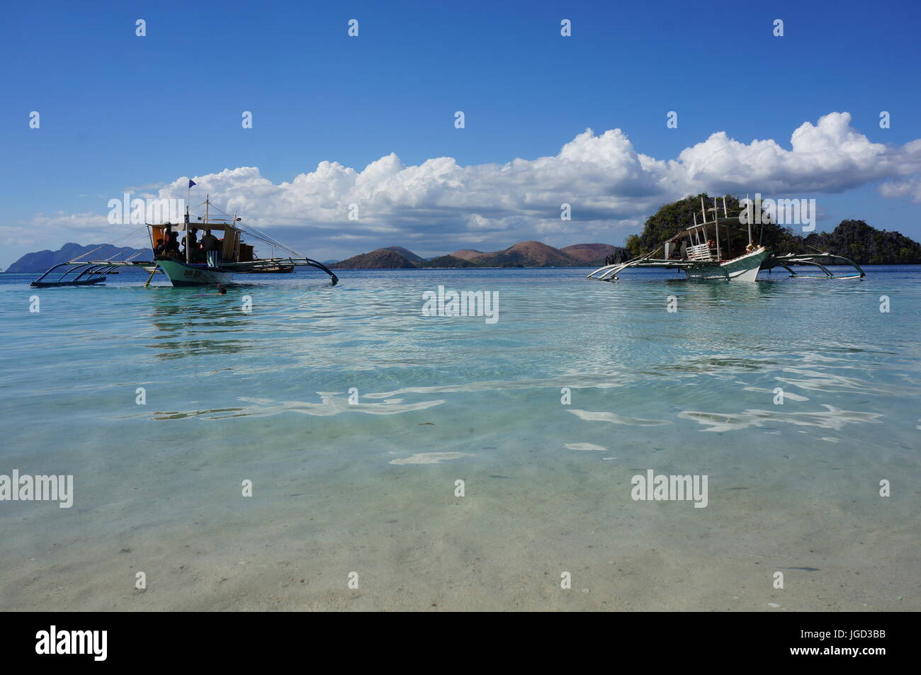 Fishing boats converted for tourists.  Low shot sand, blue sea, boats, hill range / cliffs, bright blue sky, white Stock Photo