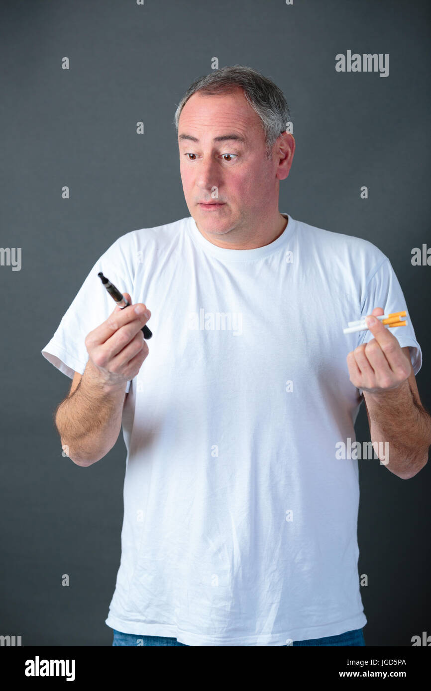 man is holding vaporizer and conventional tobacco cigarettes and comparing - Stock Image