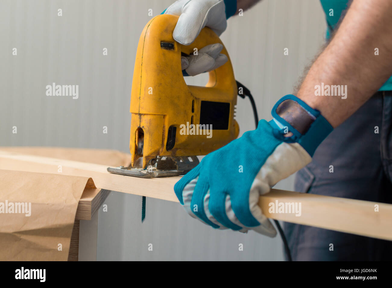 Carpenter handyman using electric handy saw on the woodwork workshop table - Stock Image