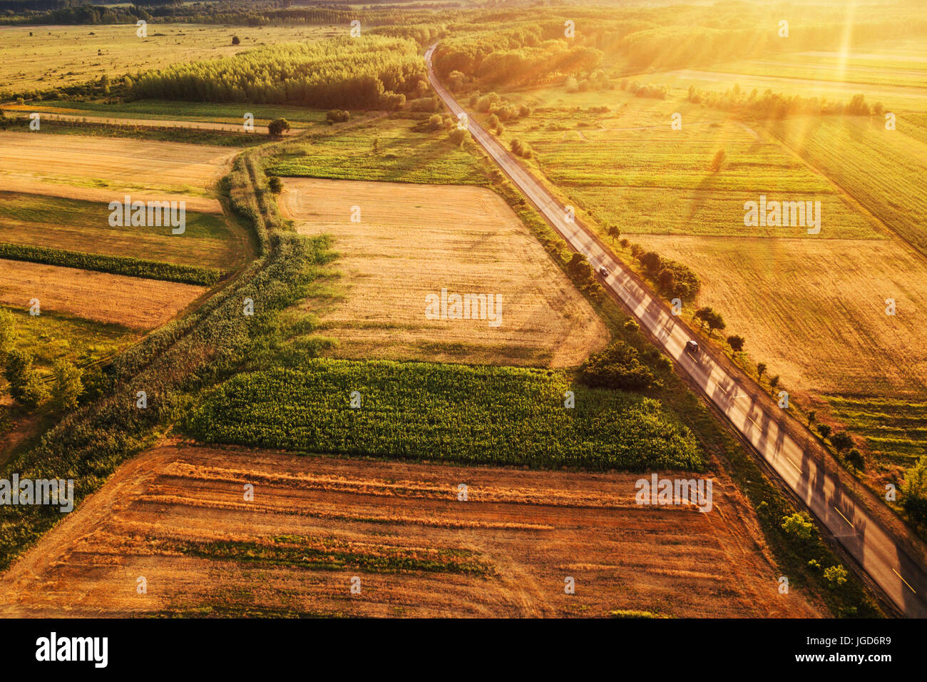 Beautiful aerial view of countryside and cultivated fields in sunset, drone point of view - Stock Image