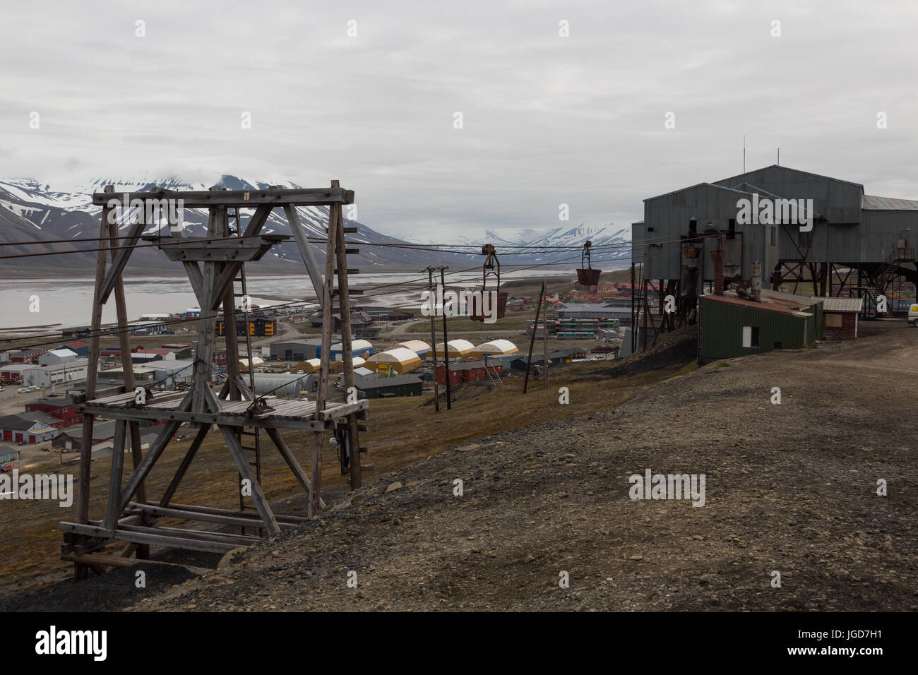 Old wooden pylons still have the coal-transport carts on overhead cables at the edge of Longyearbyen in Spitzbergen - Stock Image