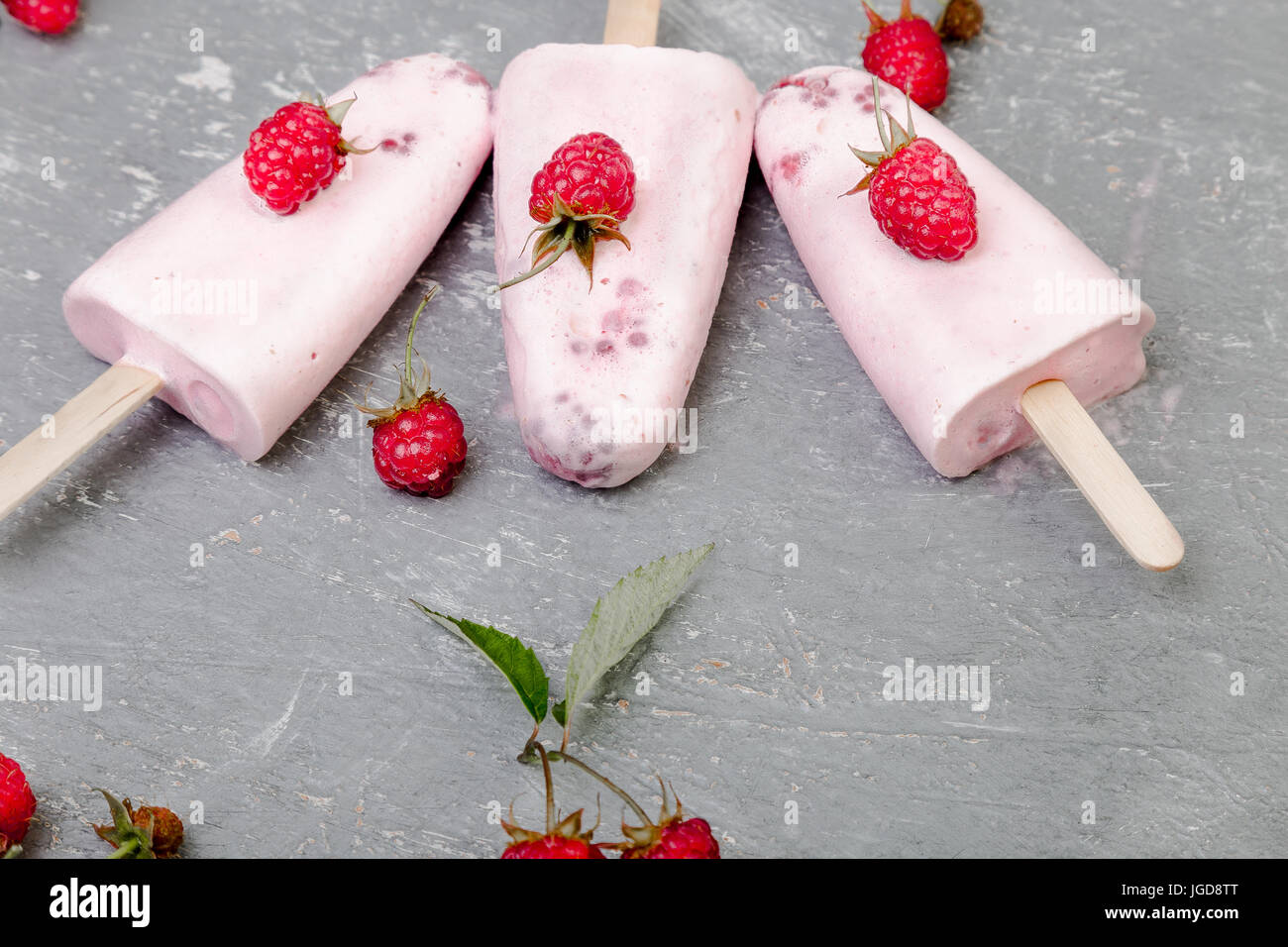 Raspberry ice cream on grey background. Three popsicles. Top view. Homemade Stock Photo