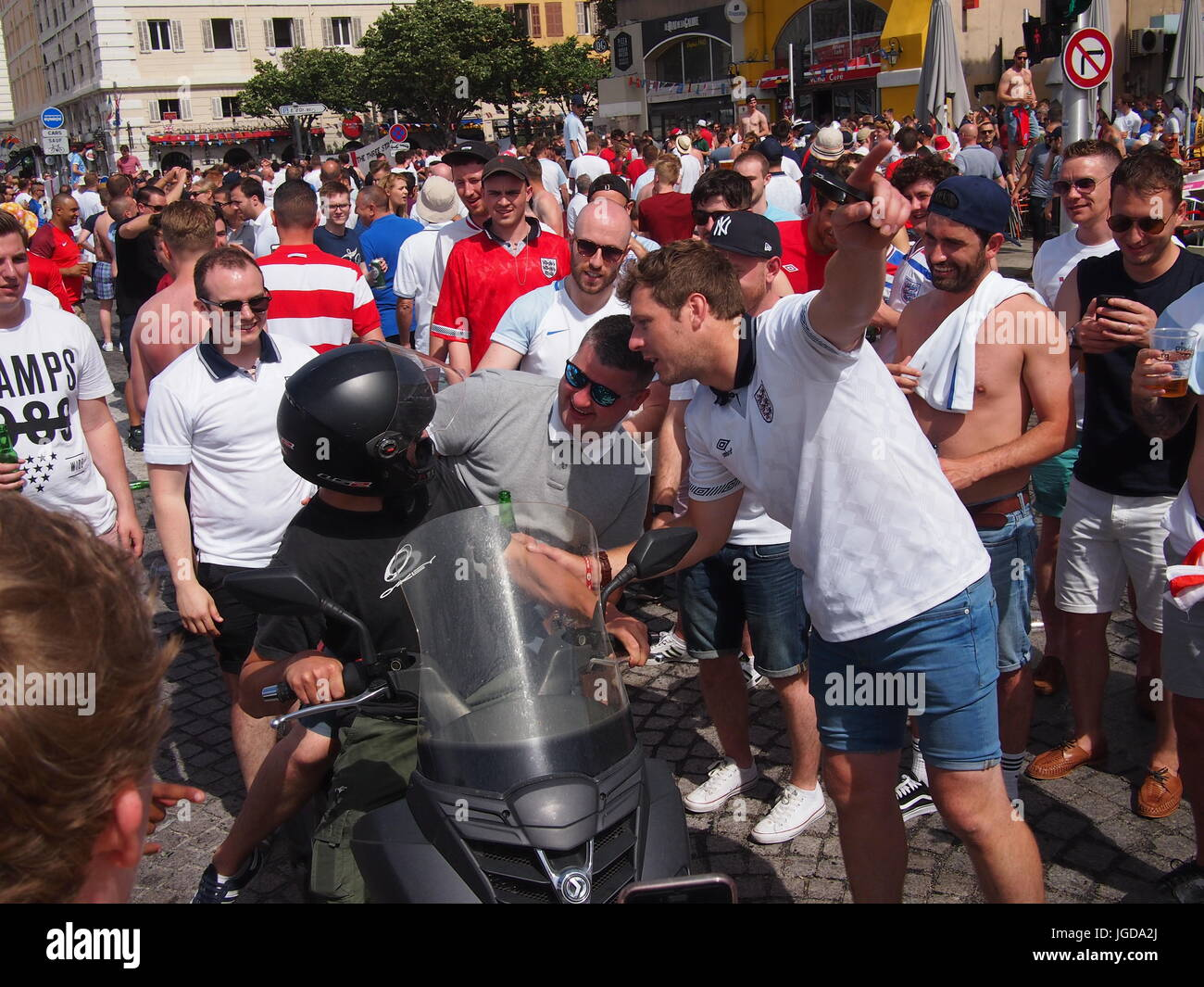 Marseille, France - June 11, 2016: England fans joking with a local on a motorbike as he tries to navigate his way - Stock Image