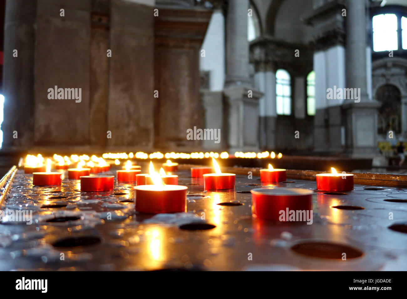 Lit prayer candles in a Catholic church, Venice, Italy - Stock Image