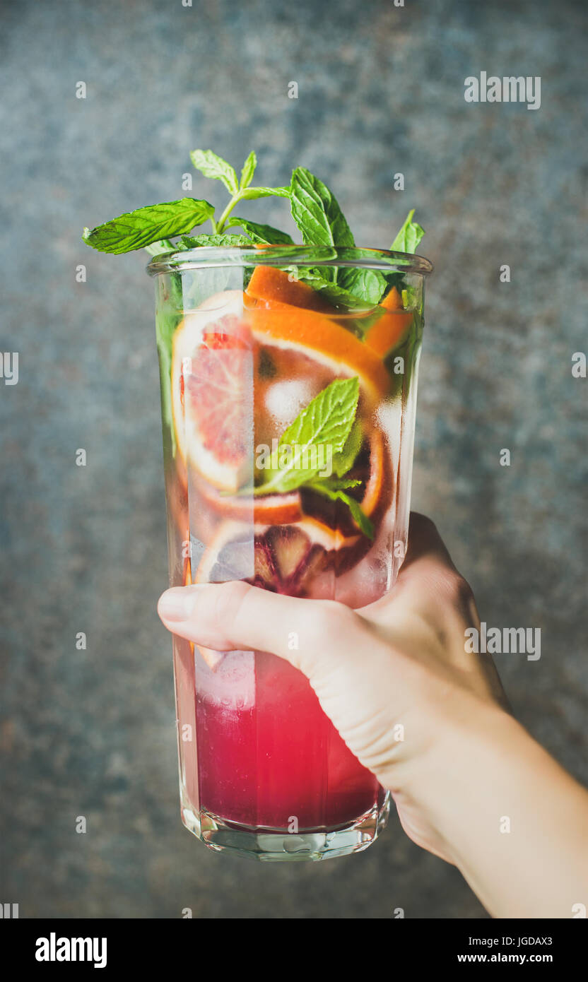 Woman's hand holding glass of homemade blood orange citrus lemonade Stock Photo