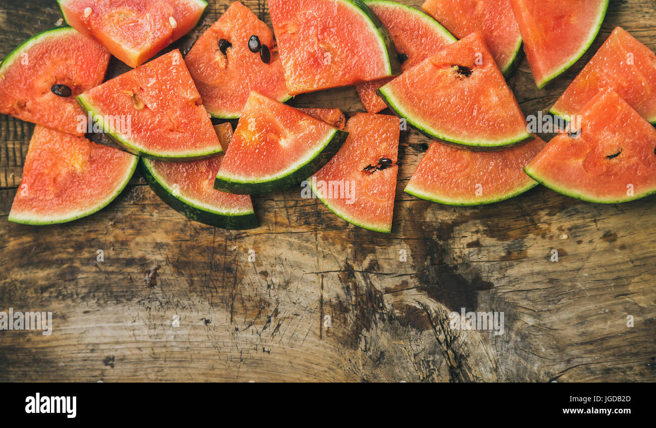 Juicy watermelon pieces over rustic wooden background - Stock Image
