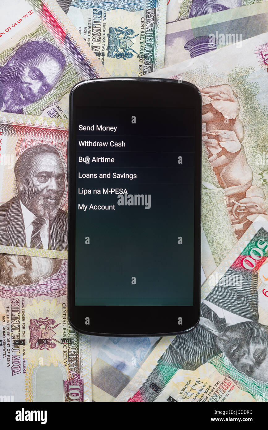 Safaricom M-Pesa fintech microfinance money transaction service on phone with Kenyan Shilling bank notes background Stock Photo
