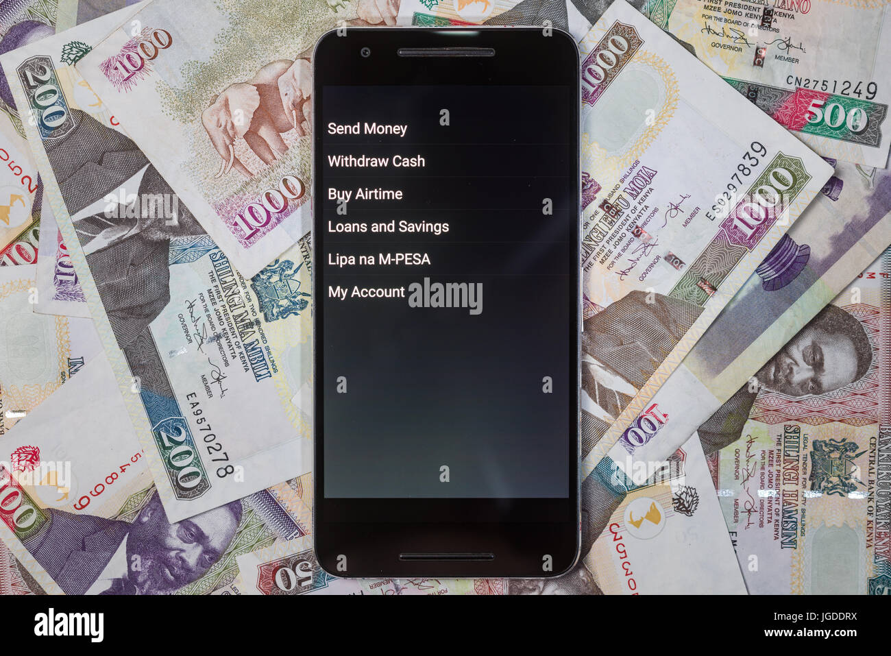 Safaricom M-Pesa fintech microfinance money transaction service on phone with Kenyan Shilling bank notes background Stock Photo