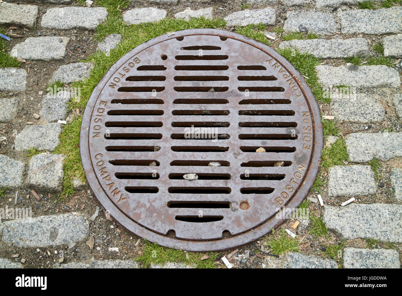 metal manhole cover for the boston edison company in cobblestoned street Boston USA - Stock Image
