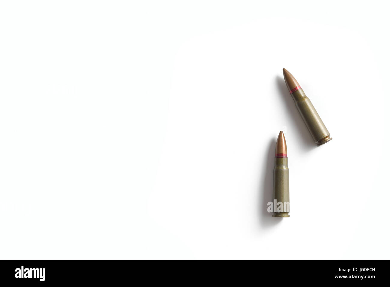 Two rifle bullets isolated on a white background. Military ammunition - Stock Image