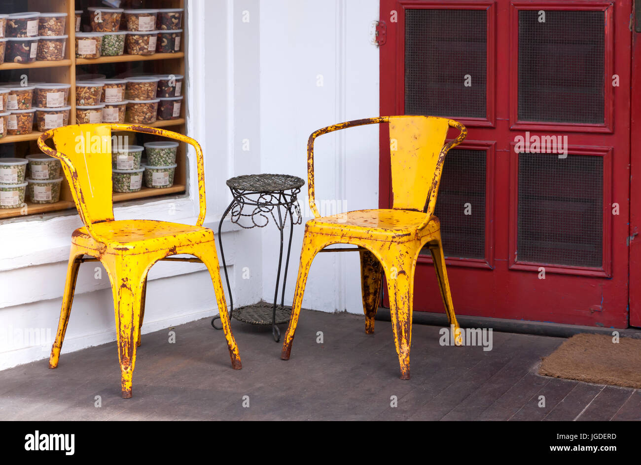 Two colorful yellow weathered metal chairs on a porch set against a red door. Stock Photo