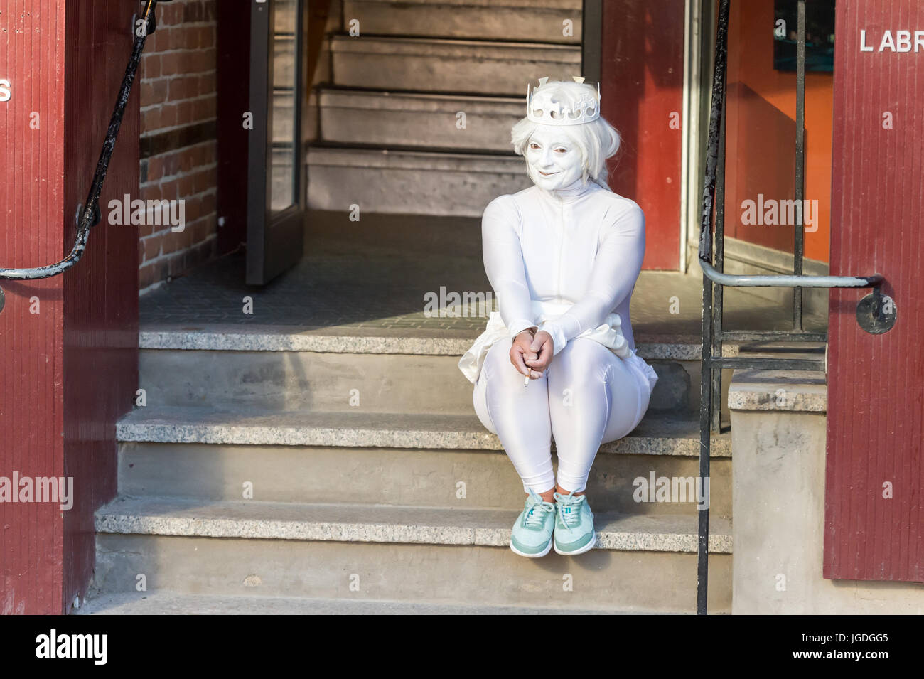 Montreal, 3 July 2017: Mime artist with white make-up and white costume taking a break at Montreal Jazz Festival Stock Photo