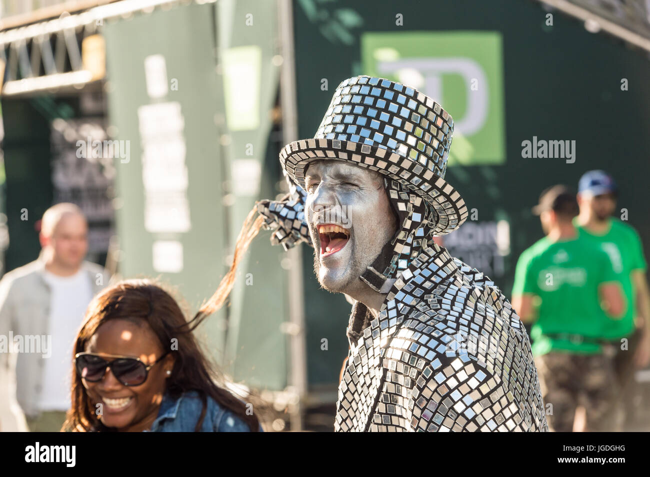 Montreal, 3 July 2017: Mime artist wearing a costume made of small mirrors having fun with a young woman - Stock Image