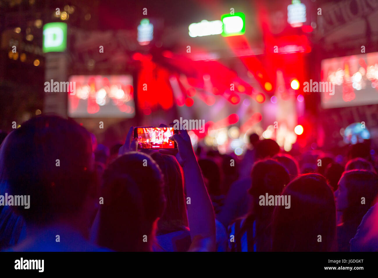 Montreal, 4 July 2017: blurred picture of audience at concert, with a girl filming the show with smart phone - Stock Image
