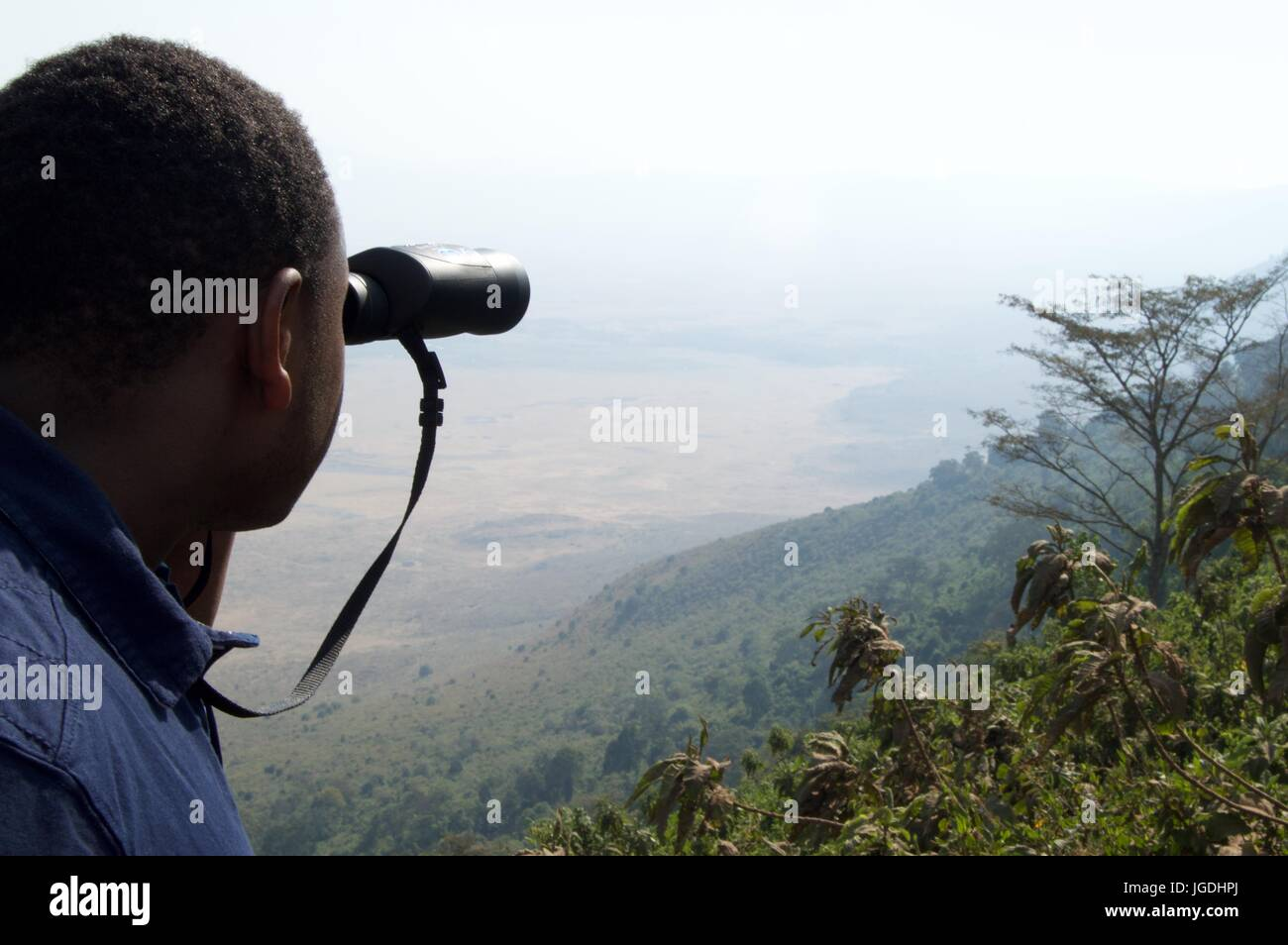 Man looks over crater rim with binoculars, Ngorongoro Crater, Tanzania - Stock Image