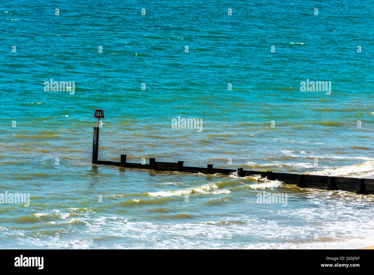 Dock pilings on a sandy beach, blue ocean and yellow sand, sunny hot day in seaside resort, summer - Stock Image
