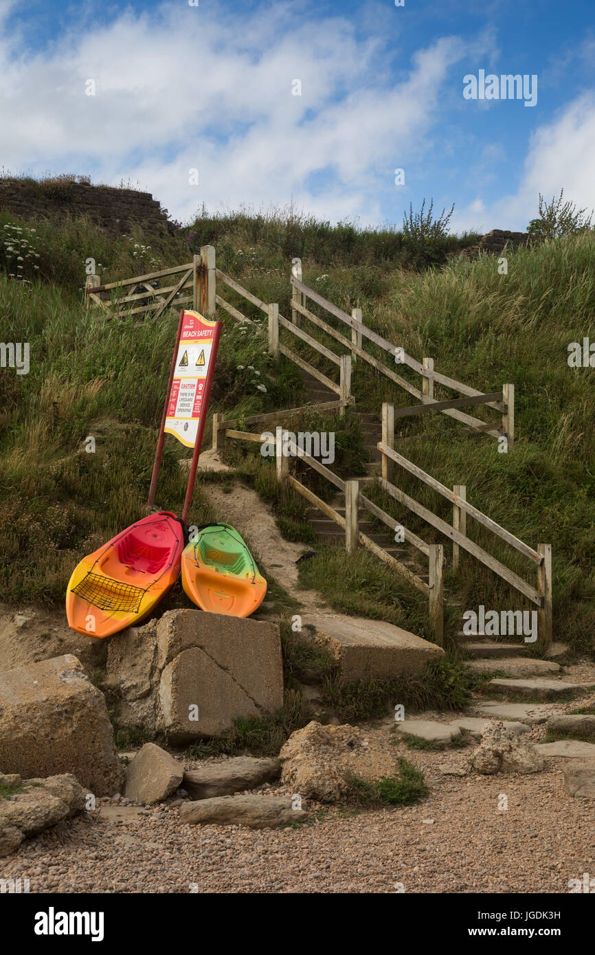 Colourful boats and crooked stone steps with wooden handrails on Jurrasic coast leading down to Eype beach, Symmondsbury, - Stock Image