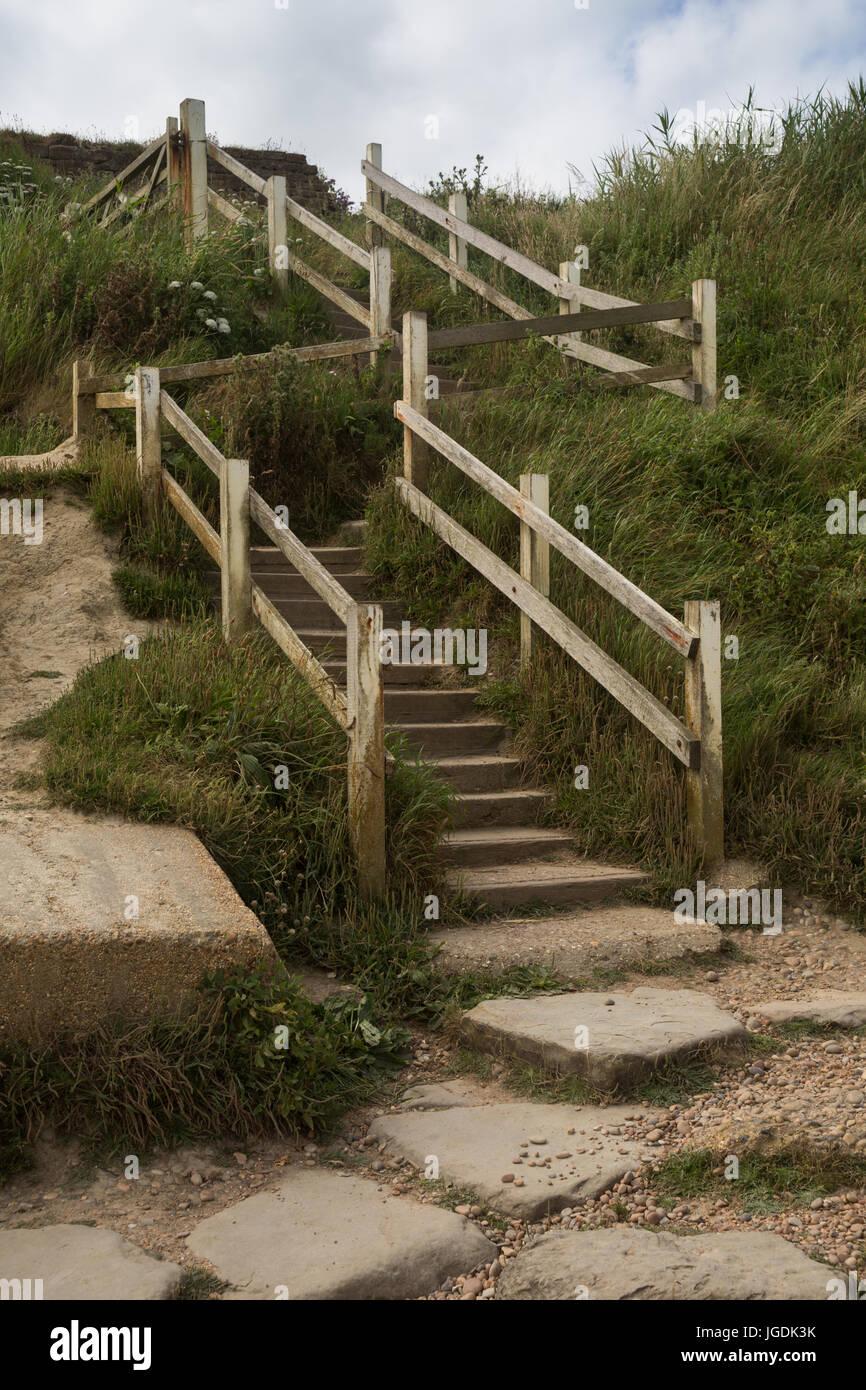 Crooked stone pedestrian steps with wooden handrails on Jurrasic coast leading down to Eype beach, Symmondsbury, Stock Photo