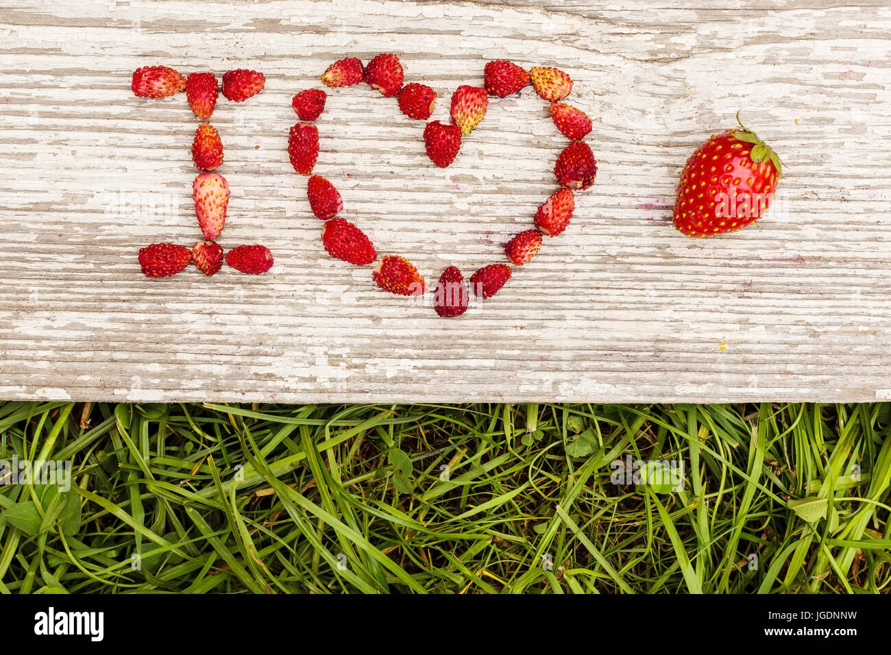 Strawberries are laid out in the letters on a background of green grass and board. - Stock Image
