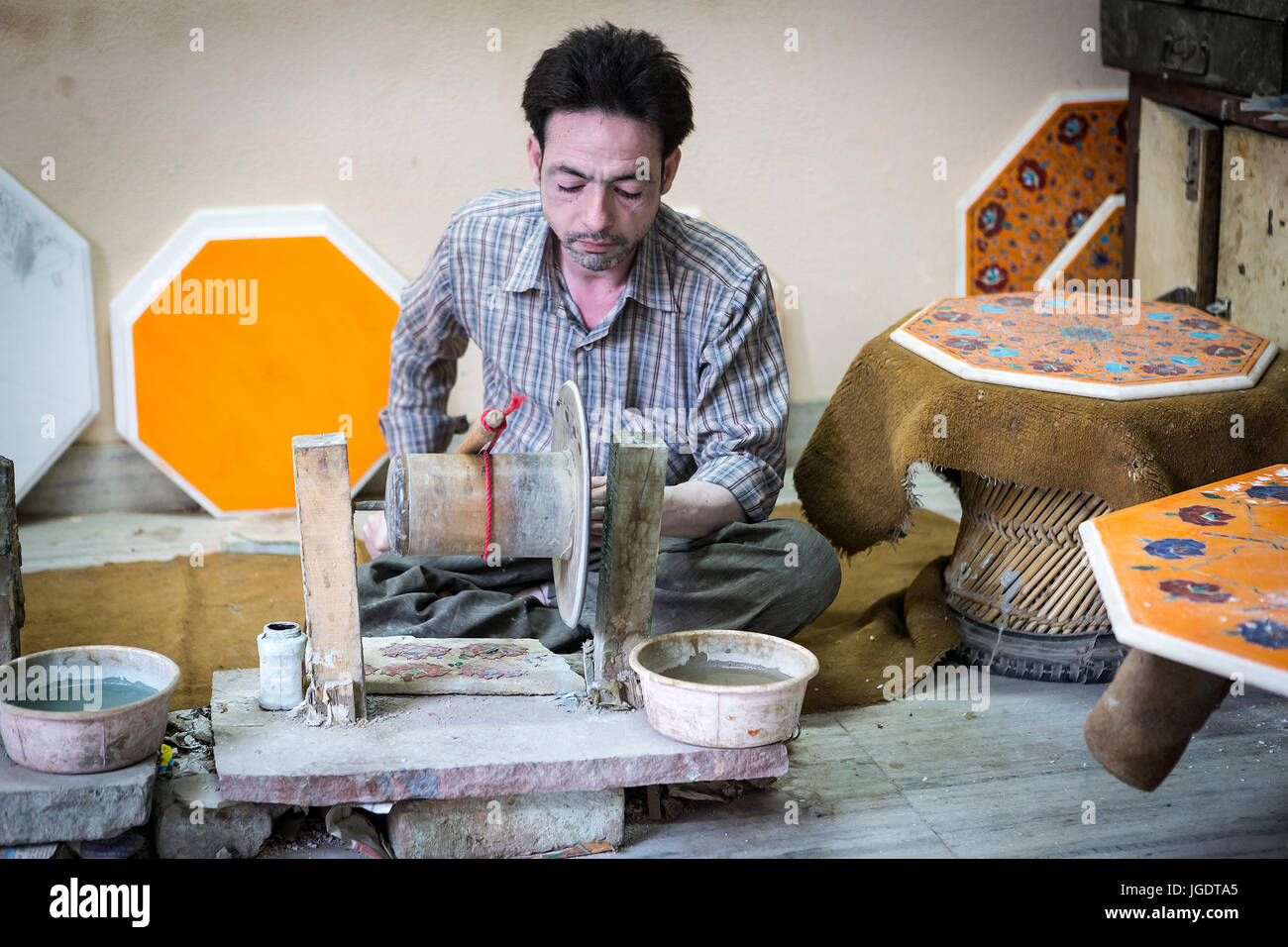 Pale skinned man in India shaping pieces of marble and semi-precious stones on a hand-powered emery wheel near to - Stock Image