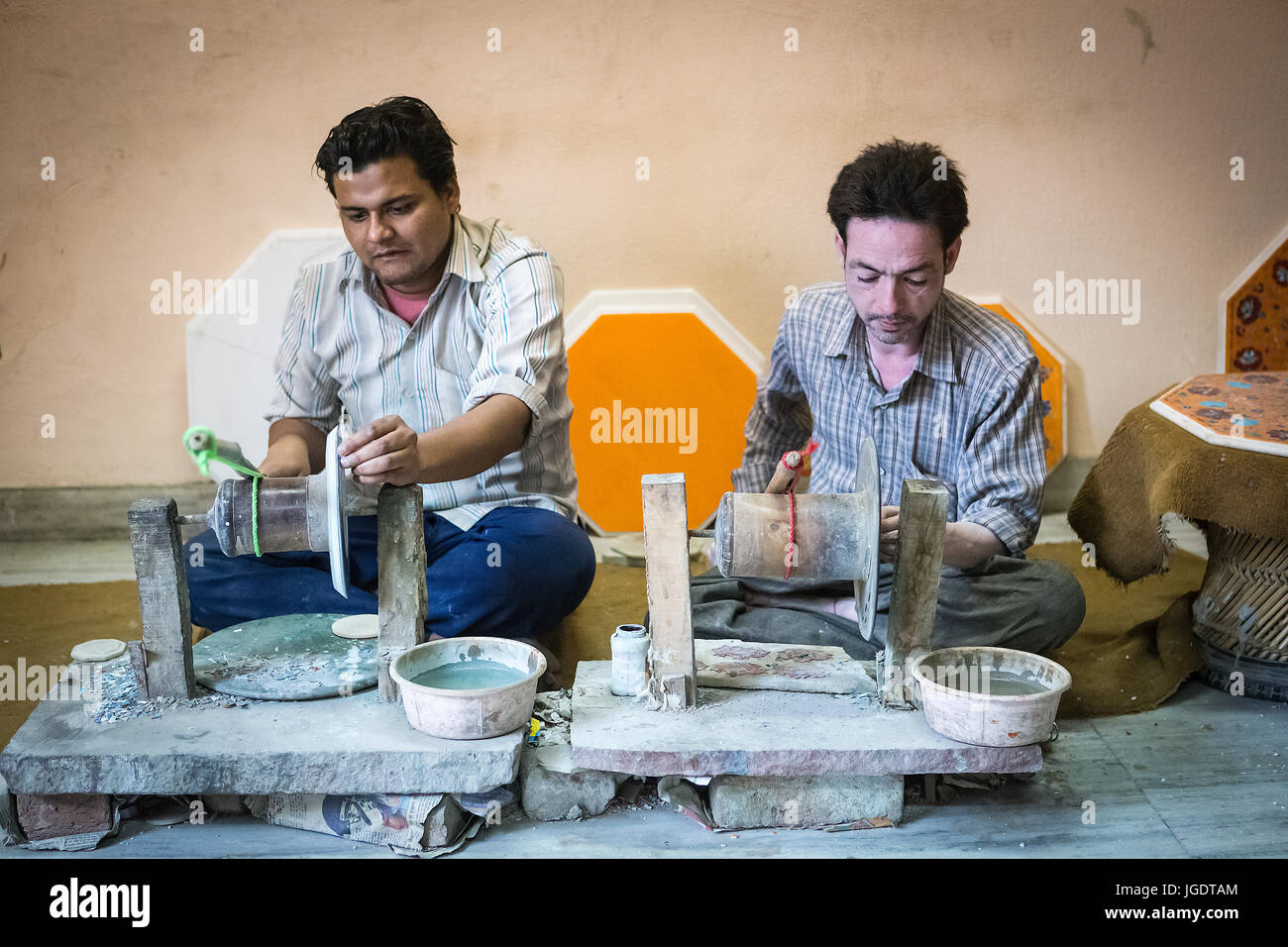 Pale skinned man and darker skinned man in India shaping pieces of marble and semi-precious stones on a hand-powered - Stock Image