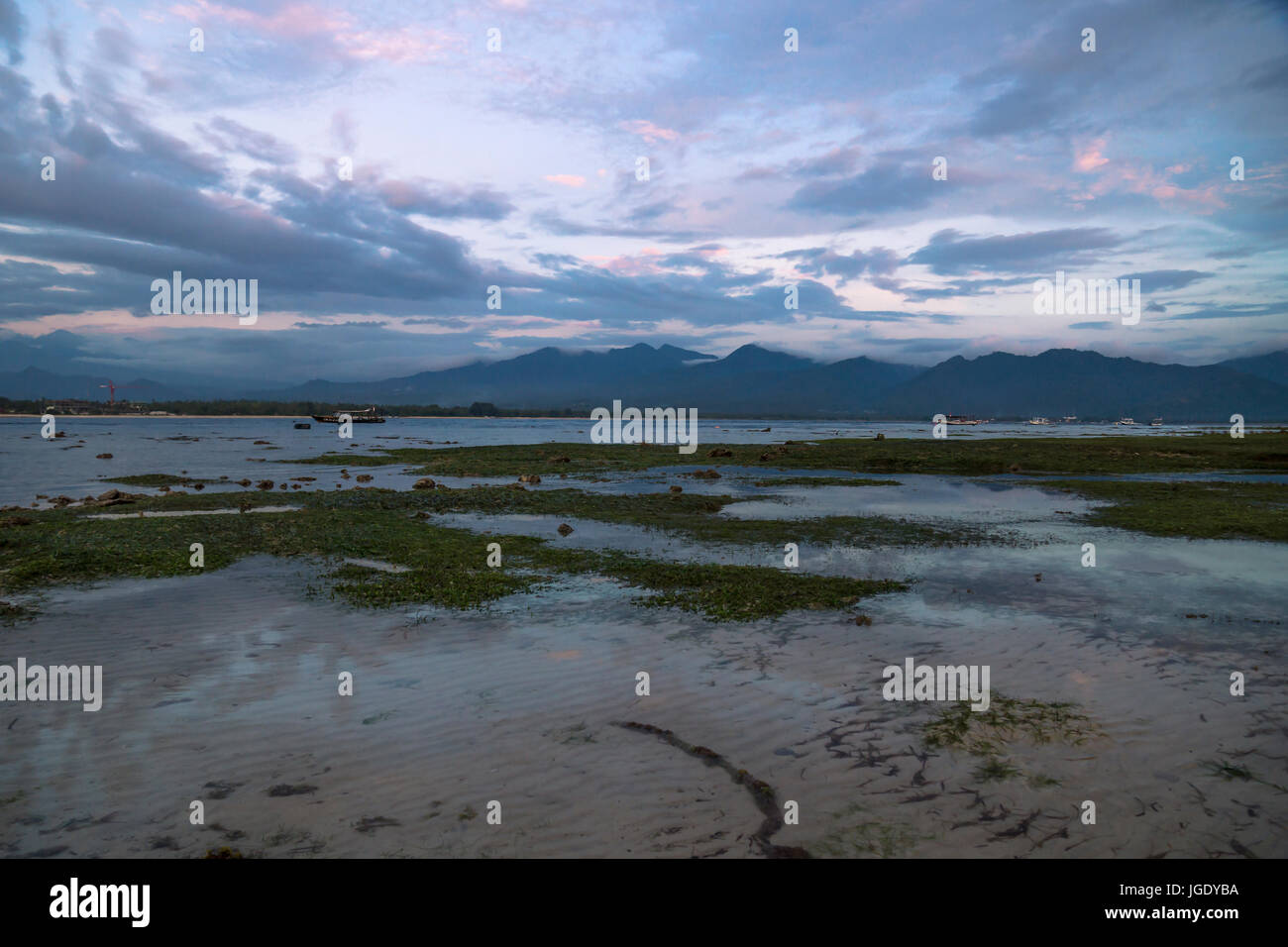 VIew to Lombok mountains from the beach of Gili Air during sunset with purple cloudscape, Indonesia - Stock Image