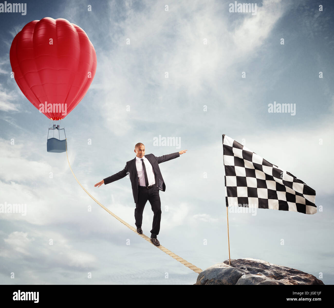 Business concept of businessman who overcome the problems reaching the flag on a rope - Stock Image