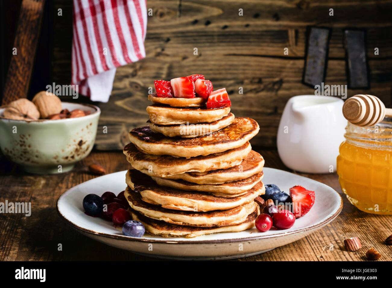 Whole meal pancakes with fresh berries and honey on wooden table. Closeup view. Rustic style stock food photo - Stock Image
