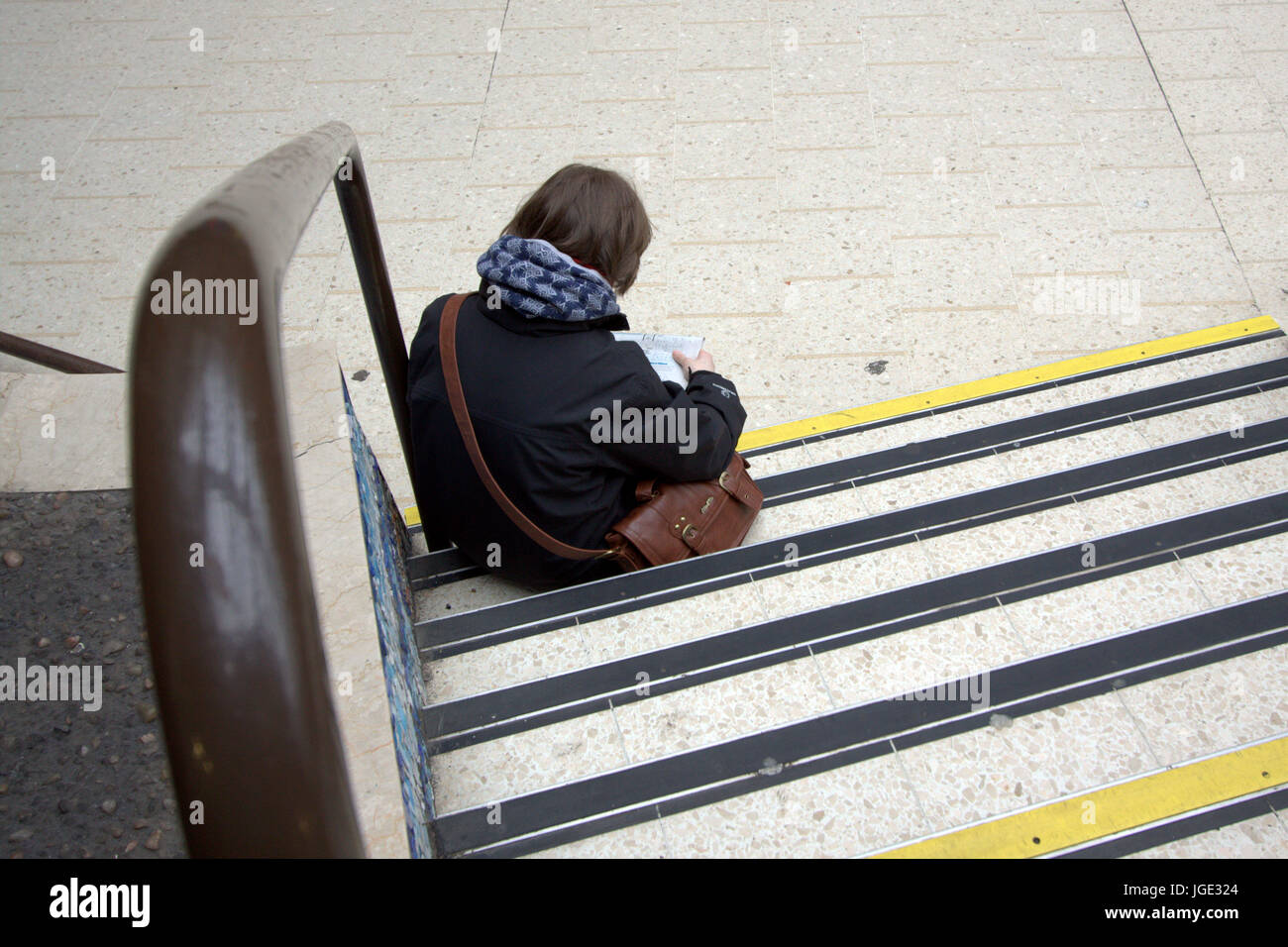commuter passenger tourist sitting on a step viewed from behind - Stock Image