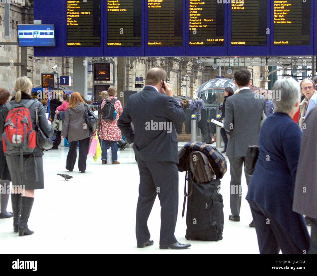 businessman on mobile phone in Glasgow Central  train station in front of departures board - Stock Image