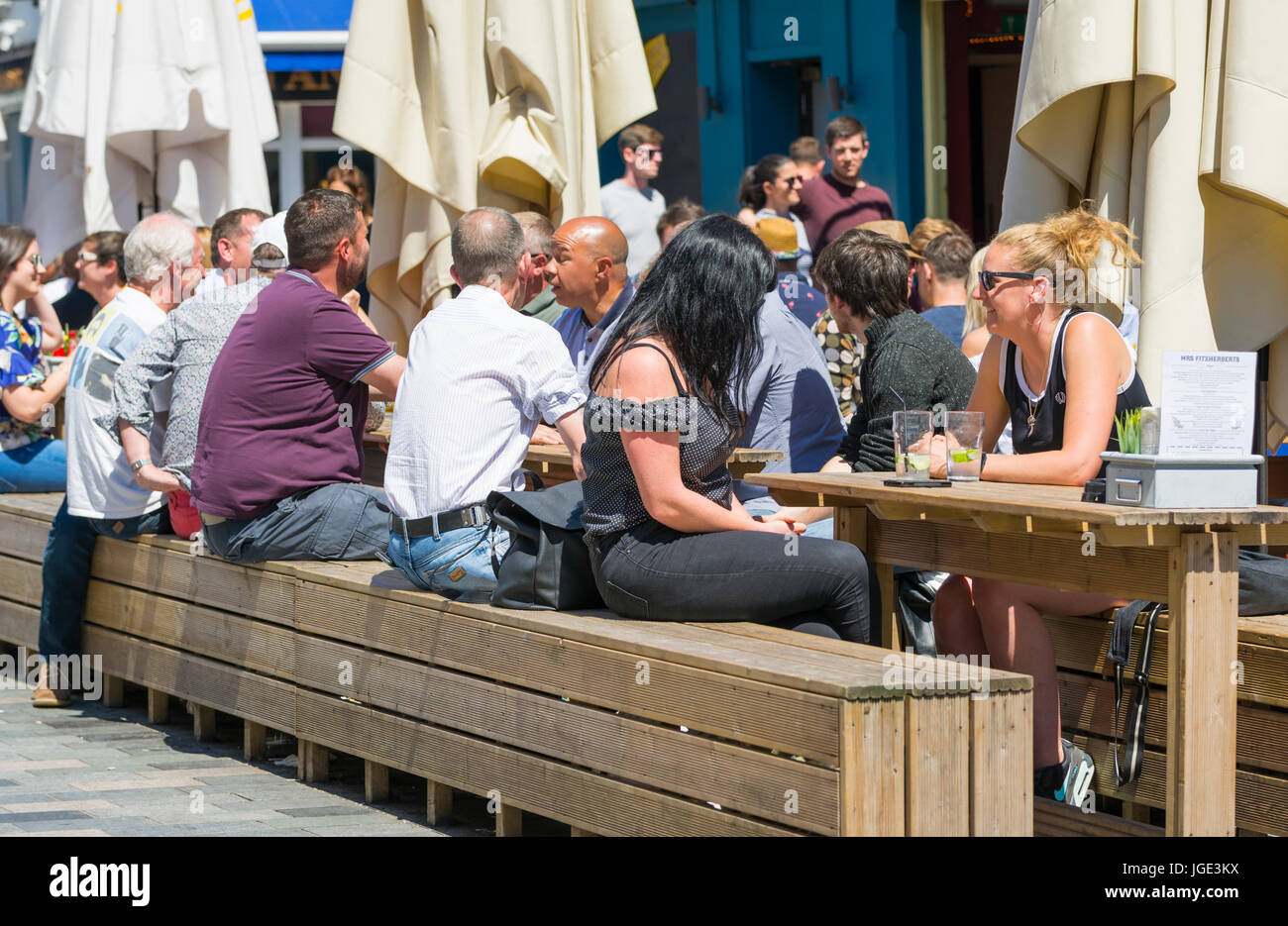 People sitting outside on wooden tables and benches at a cafe and bar on a hot day in Summer. - Stock Image