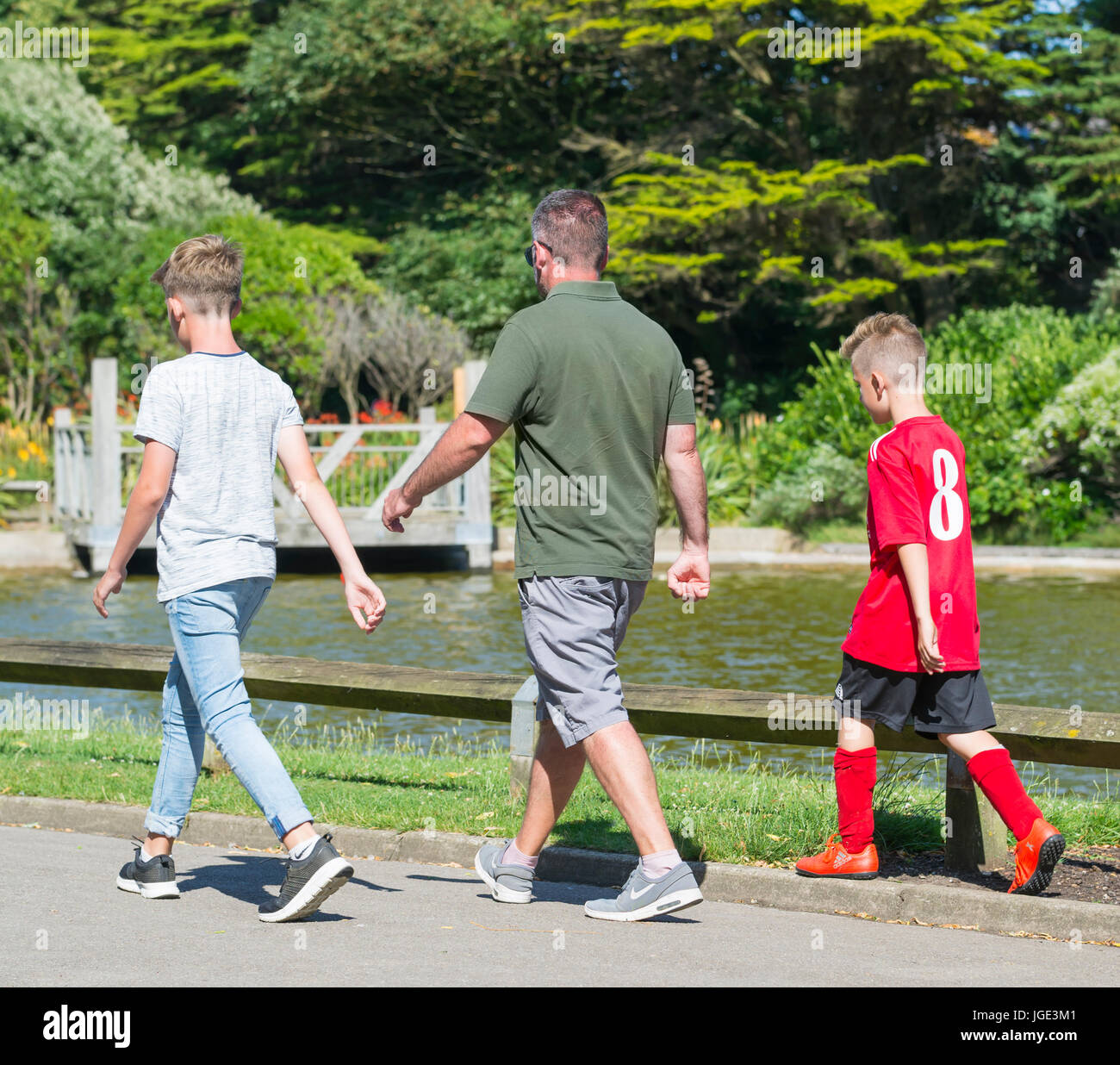 Father and Sons walking together through a park on a warm day in Summer. - Stock Image