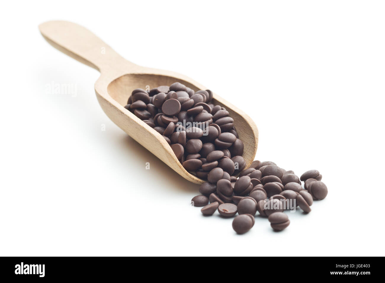 Tasty chocolate morsels in wooden scoop isolated on white background. - Stock Image
