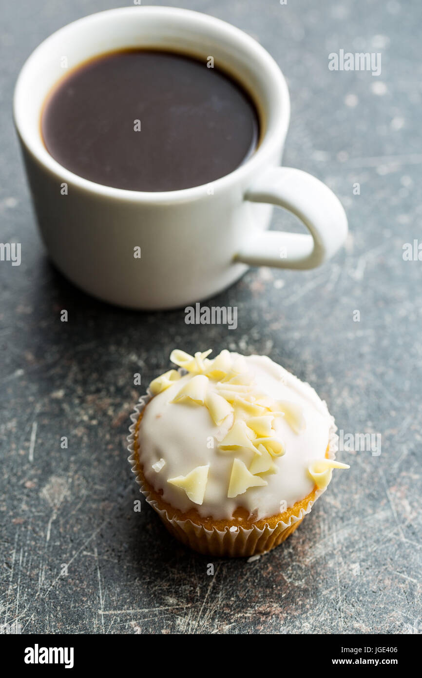 Tasty cupcake and coffee cup on kitchen table. - Stock Image