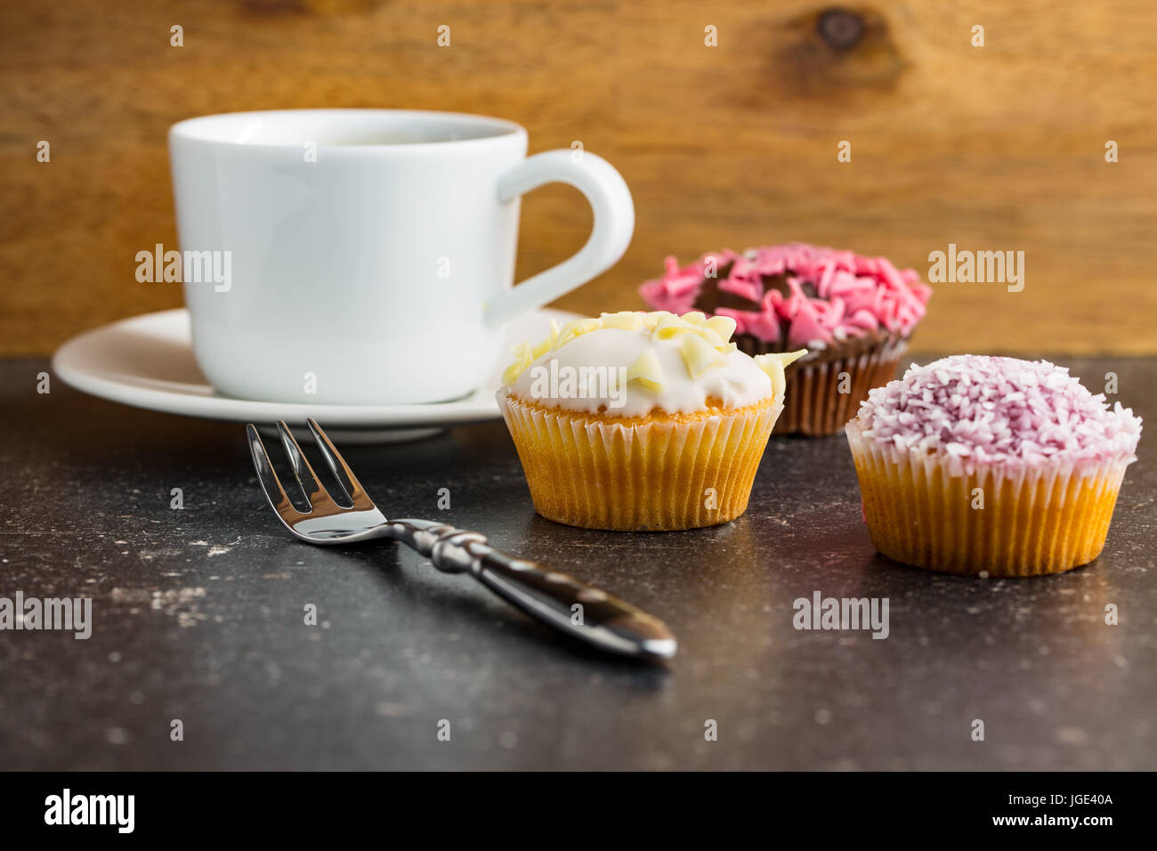 Tasty sweet cupcakes and coffee cup. - Stock Image