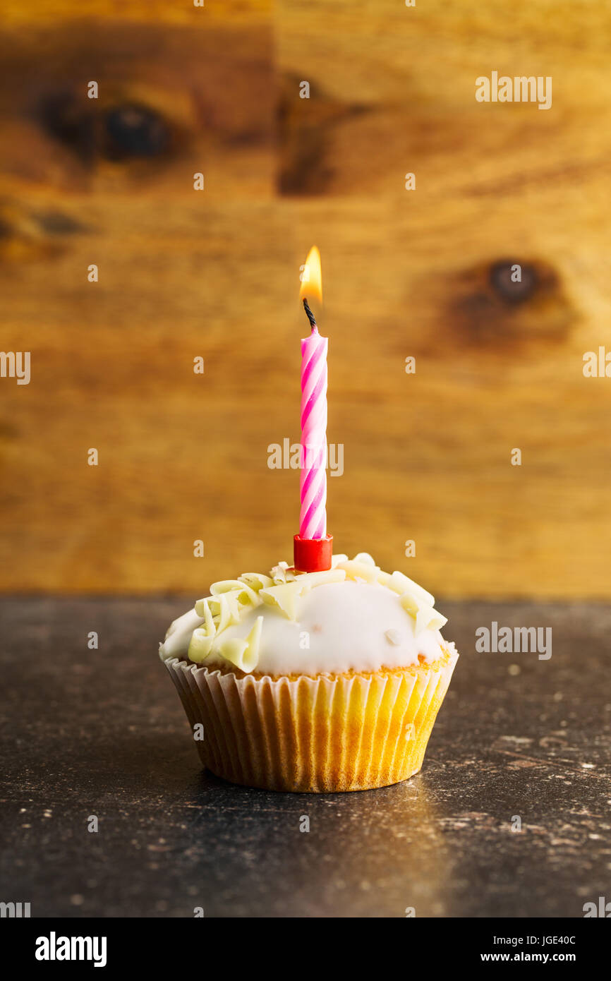 Cupcake with burning candle on table. - Stock Image